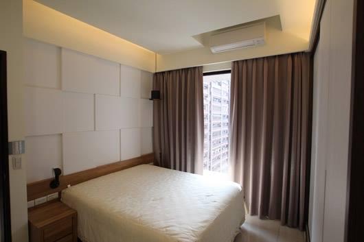 走廊與主臥室以壁紙與木作結合,使裡外有延續性。臥室床頭主牆以白格搭配木頭櫃,溫暖色調帶出自然、純樸的氣息。