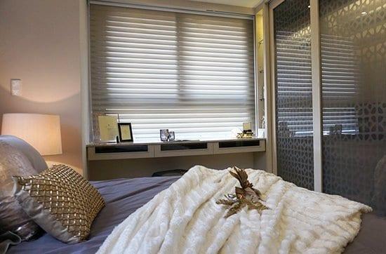 調光捲簾製造朦朧微透光的氛圍,搭配暖暖色調的床頭燈